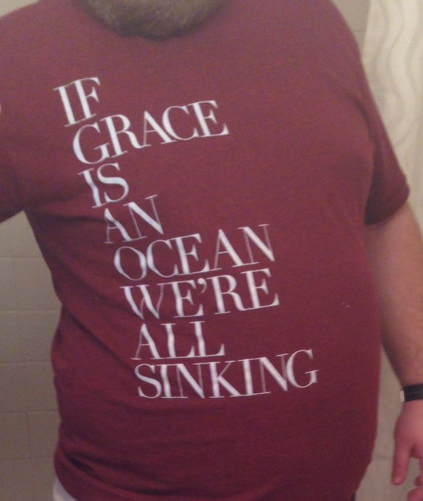 Photo of a maroon shirt with 'If Grace Is An Ocean We're All Sinking' printed on it.